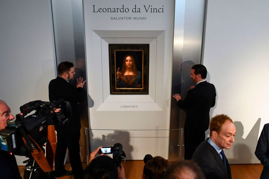 """Security personnel stand next to Leonardo da Vinci's """"Salvator Mundi"""" after it was unveiled at Christie's in New York on October 10, 2017. Photo credit should read Jewel Samad /AFP/Getty Images."""